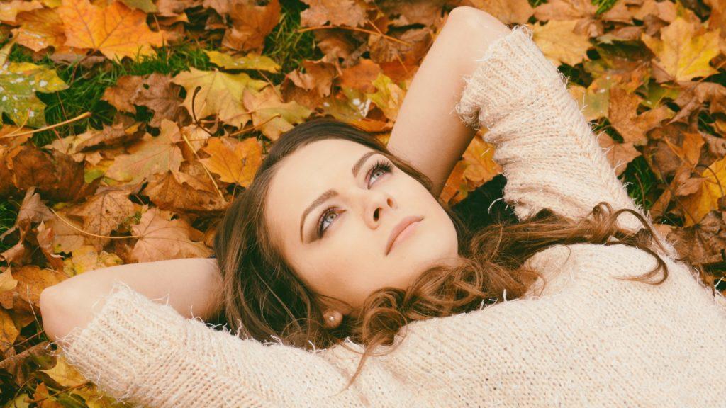 Frau liegt im Herbstlaub und starrt nach oben.
