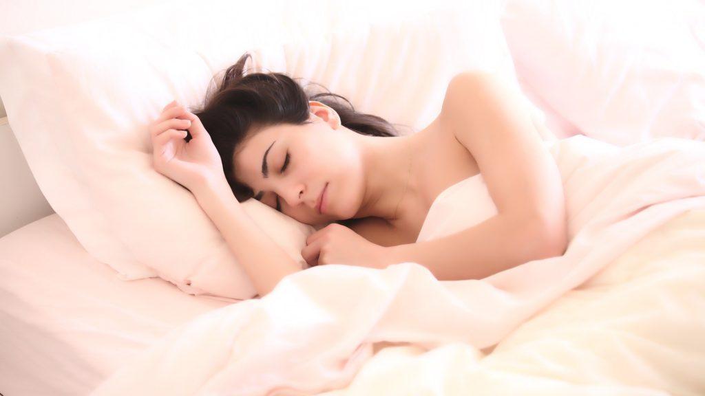 Frau liegt im weißen Bett und schläft.