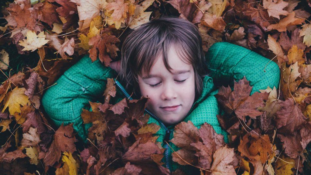 Ein Kind schläft im Herbstlaub.